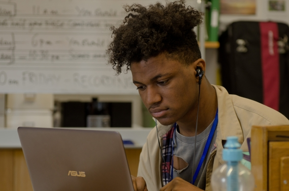 A young black man with earphones on his laptop